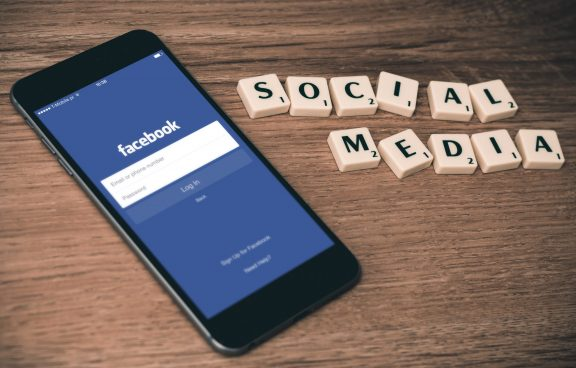 space gray iPhone 6 with Facebook log-in display near Social Media scrabble tiles